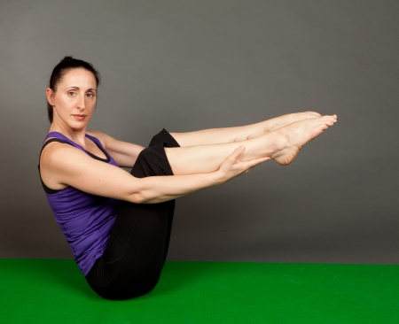 Studio shot of a fit brunette woman doing yoga stretching and flexibility exercises on a grey background Stock Photo - 13904297