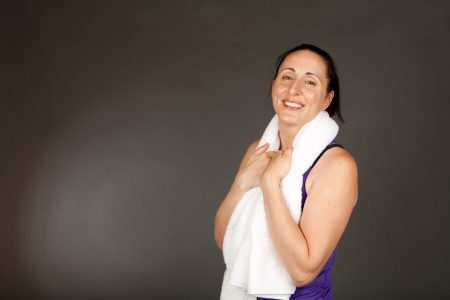 perspiring: Adult sweating woman with towel after a workout