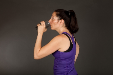 perspiring: Adult sweating woman drinking a glass of water after a workout