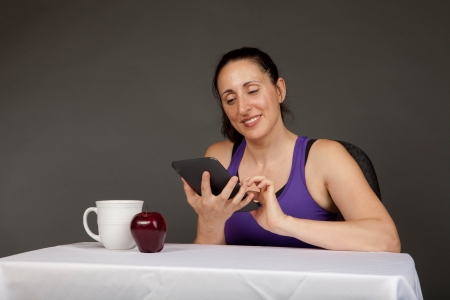 Happy fit girl after a workout sitting with an electronic reader and a snack photo