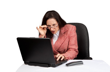 An adult businesswoman wearing a suite on a isolated white background working on a laptop with a phone on her desk photo