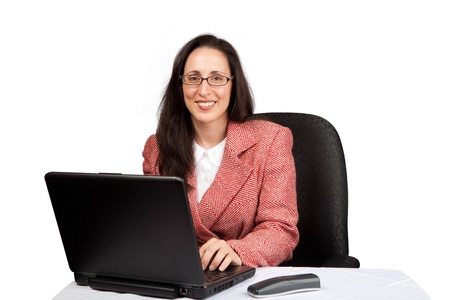An adult businesswoman wearing a suite on a isolated white background working on a laptop with a phone on her desk Stock Photo - 13905277