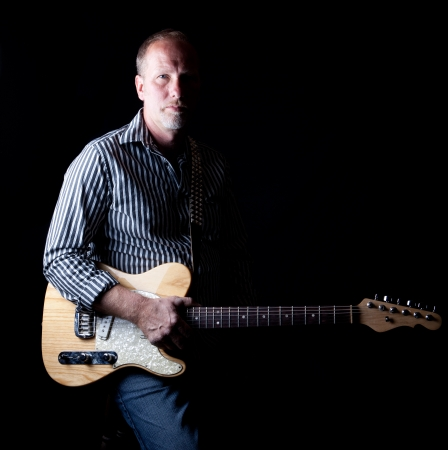 Low key portrait of a middle aged musician holding an electric guitar with high contrast shadow filled lighting Stock Photo - 13905376