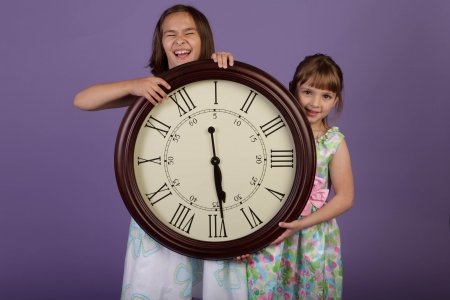 Two grade school kids holding a large wall clock with roman numerals