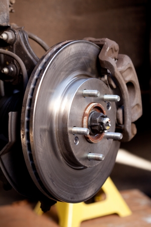 Close up shot of a newly replaced brake rotor and pads for a modern car photo