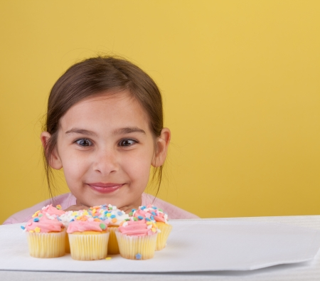 yo: Young girl staring cross eyed at a bunch of cupcakes  on a yellow background