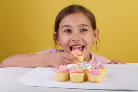 yo: Young girl eating cupcakes with big brown eyes on a yellow background Stock Photo