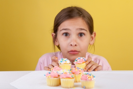 Young girl caught stealing two cupcakes with a guilty expression on a yellow background photo