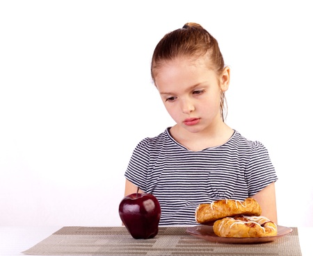 health care decisions: Studio shot of a child staring at an apple with a tempting danish on the side.