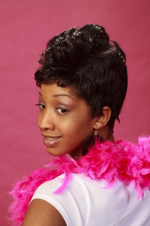 Portrait of a beautiful black woman with a feather boa on a pink background (one of a series)