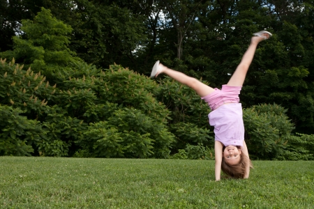 action shot: Outdor action shot of a little girl in pink doing a cartwheel with motion in her legs Stock Photo