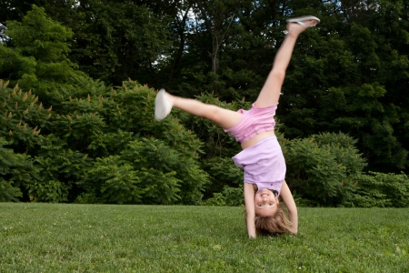 Outdor action shot of a little girl in pink doing a cartwheel with motion in her legs Stock Photo