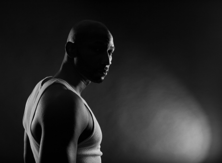 bald men: Strong contrast shot of  a young, handsome, muscular black man in shadows.