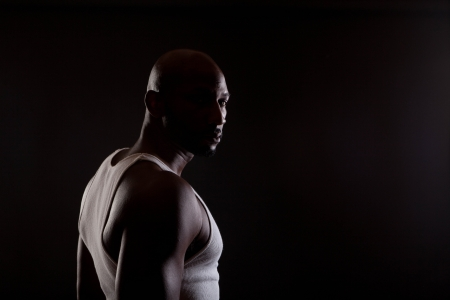 shadow: Strong contrast shot of  a young, handsome, muscular black man in shadows.