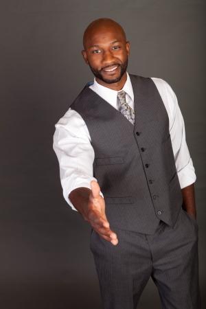 black business man: Jeune homme d'affaires noir tendre la main.