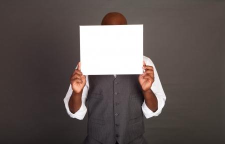 black business man: Jeune homme d'affaires noir tenant une carte blanche en face de son visage