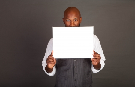 Young black business man holding a white card in front of his face Stock Photo - 14447941