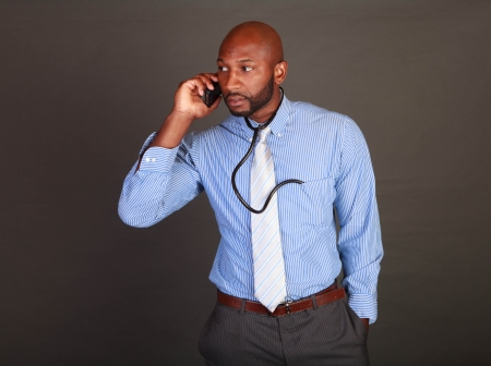 African American / Black doctor checking his cell phone photo