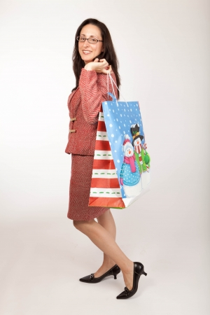 Studio shot of a woan wearing a festive red and white tweed suite carrying a christmas gift shopping bag