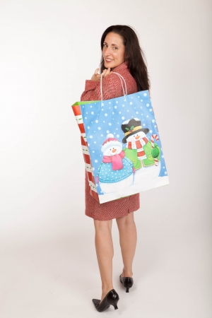 Studio shot of a woan wearing a festive red and white tweed suite carrying a christmas gift shopping bag Stock Photo - 15170559