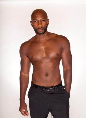 torso nudo: Ritratto di un bodybuilder con fisico muscoloso posa contro sfondo bianco con abito pantaloni