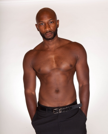 shirtless guy: Portrait of a bodybuilder with muscular physique posing against white background with dress pants Stock Photo
