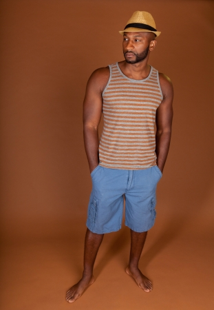 Young fit man in a casual outfit against an earthtone background photo