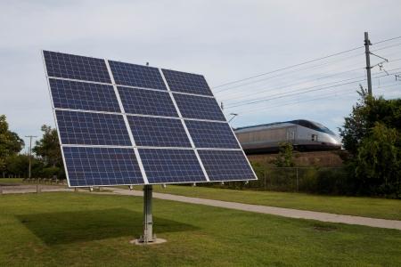 Small solar panel next to train tracks promoting green energy photo