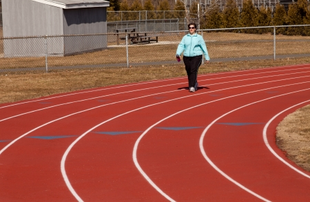 40 year old overweight woman walking around the high school track photo