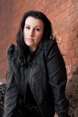 40 something: Brunette 40 something woman posing outside inn very early spring smiling confidently, plenty of room for copy