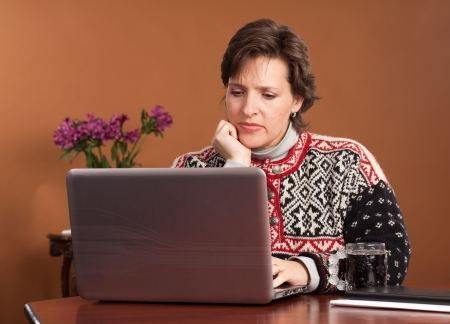 Attractive woman working shopping from home wearing a winter sweater with a cup of black coffee Stock Photo - 16084957