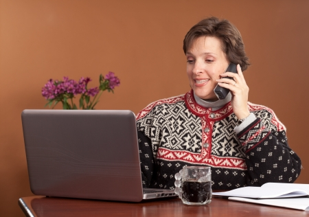 Attractive woman working shopping from home wearing a winter sweater with a cup of black coffee Stock Photo - 16084936