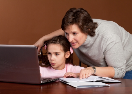 Mother and Daughter work on homework together at the kitchen table photo