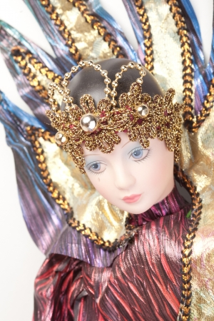 Studio shot of a doll isolated on white dressed in a Venetian carnival mardi gras costume with a tear on her face photo