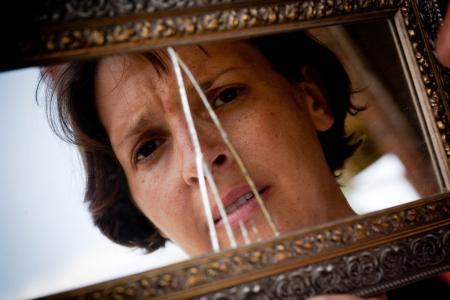 broken through: Woman looking sad and lost through a broken mirror
