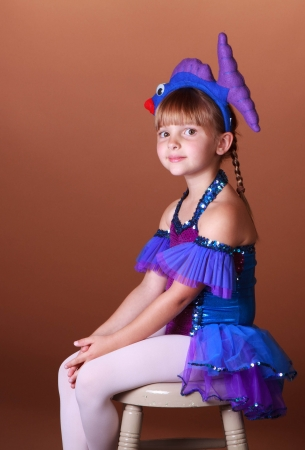 5 year old girl: 5 Year old girl with dancing costume on a brown background Stock Photo