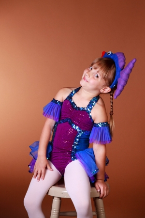 5 year old: 5 Year old girl with dancing costume on a brown background Stock Photo