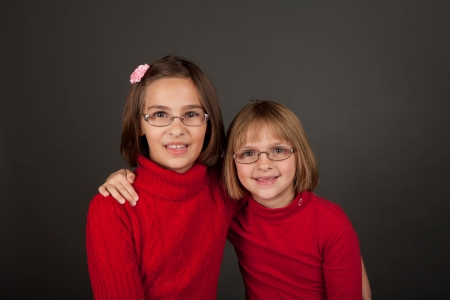 two persons only: Two young girls with glasses in a bright red sweater Stock Photo