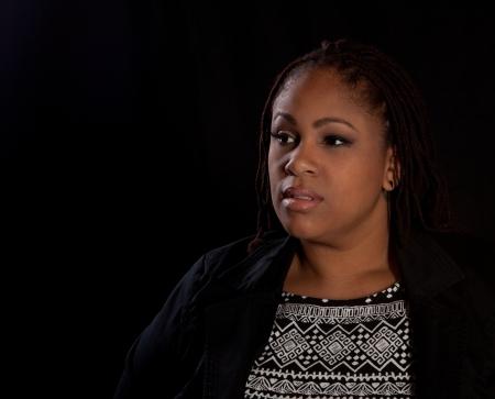 Beautiful plus size black woman on a dark background