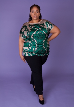 Beautiful plus size black woman standing on a purple background Stock Photo