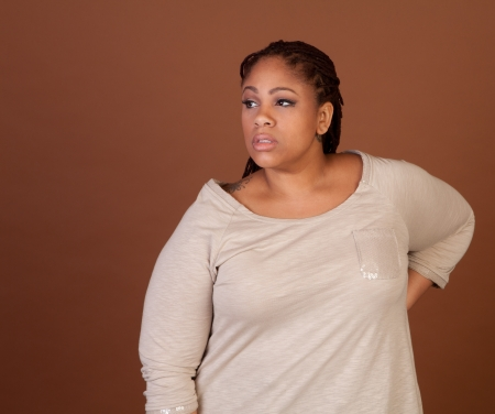 Beautiful plus size black woman standing on a brown background