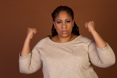 Angry beautiful plus size black woman standing on a brown background Stock Photo