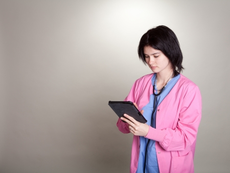 Young female doctor nurse in scrubs working on a tablet electonic medical record EMR system - part of a series