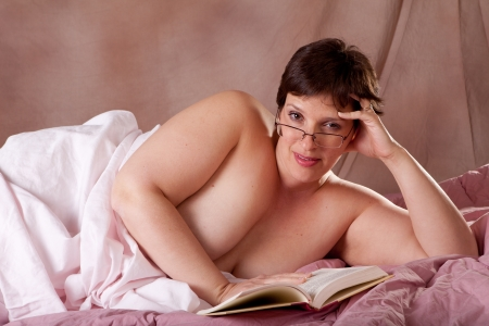 Sexy brunette topless reading in bed with glasses