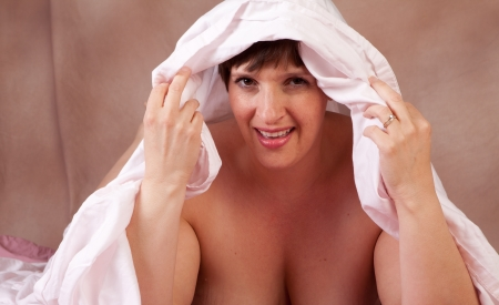 Sexy brunette topless peeking out from under the sheets with a smile Stock Photo