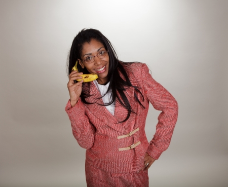 Dark skinned business woman in retro outfit with a banana phone. Part of a series. photo
