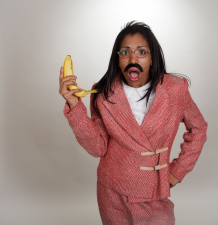phone business: Dark skinned business woman in retro outfit with a banana phone  Part of a series