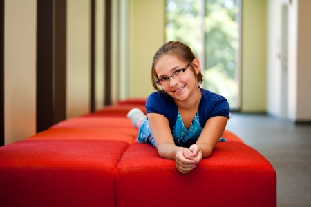 Little girl on a bench in a sunny room gesturing with room for copy