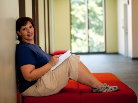 Attractive middle aged woman sitting on a bench writing in her journal room for copy Stock Photo