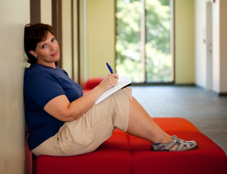 journals: Attractive middle aged woman sitting on a bench writing in her journal room for copy Stock Photo